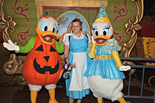 Women in Belle Cosplay with Donald and Daisy in Halloween costumes during Mickey's Not so Scary Halloween Party