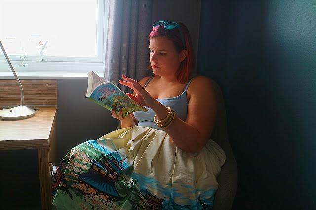 girl setting in a chair in the Travelodge Brighton reading a book