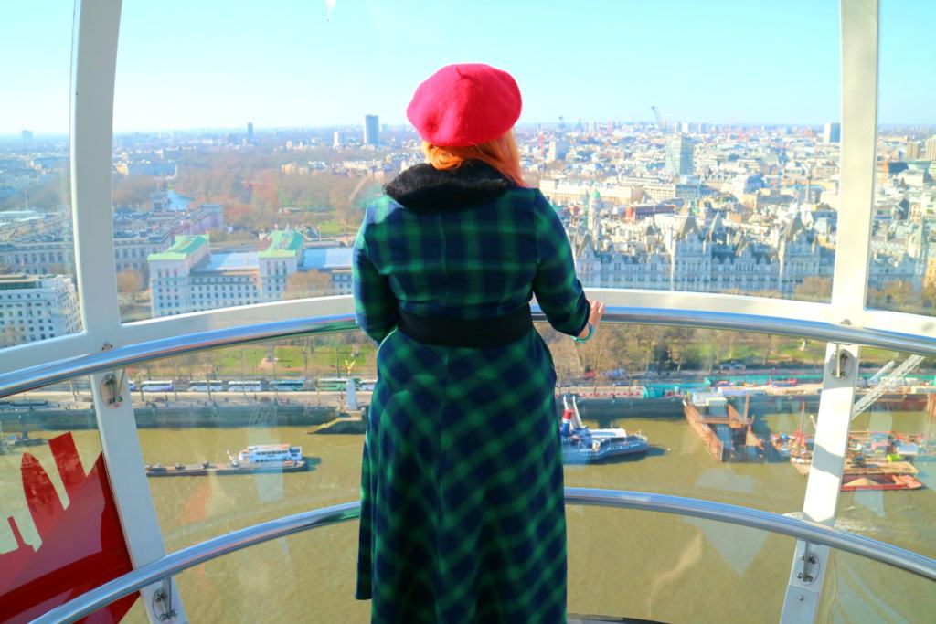 women in green dress looking out from a London Eye casual