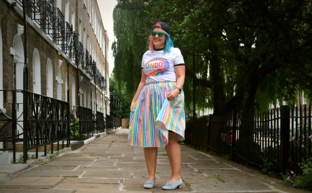 girl standing in a street with colourful hair and clothes pride fashion