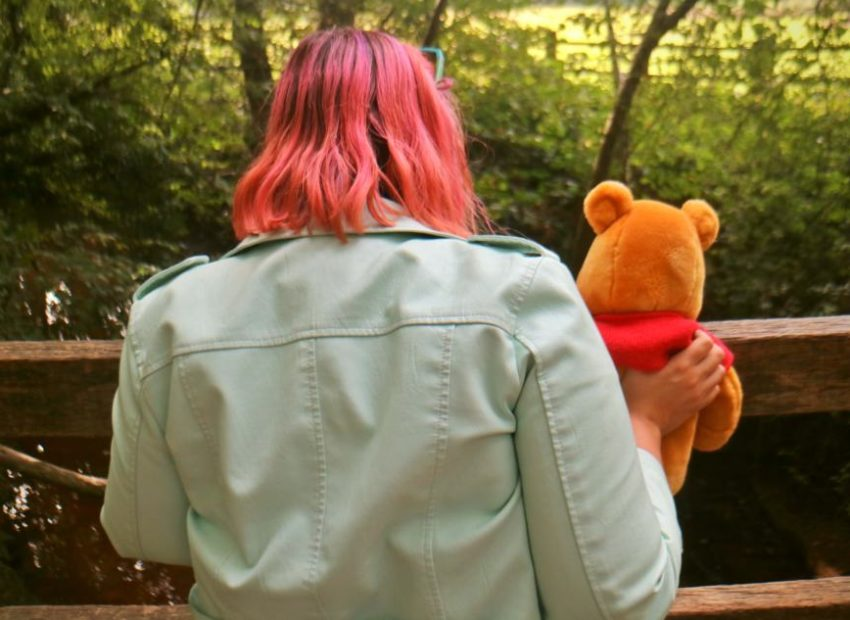 Pink haired women and Pooh Bear teddy looking over Pooh Stick Bridge