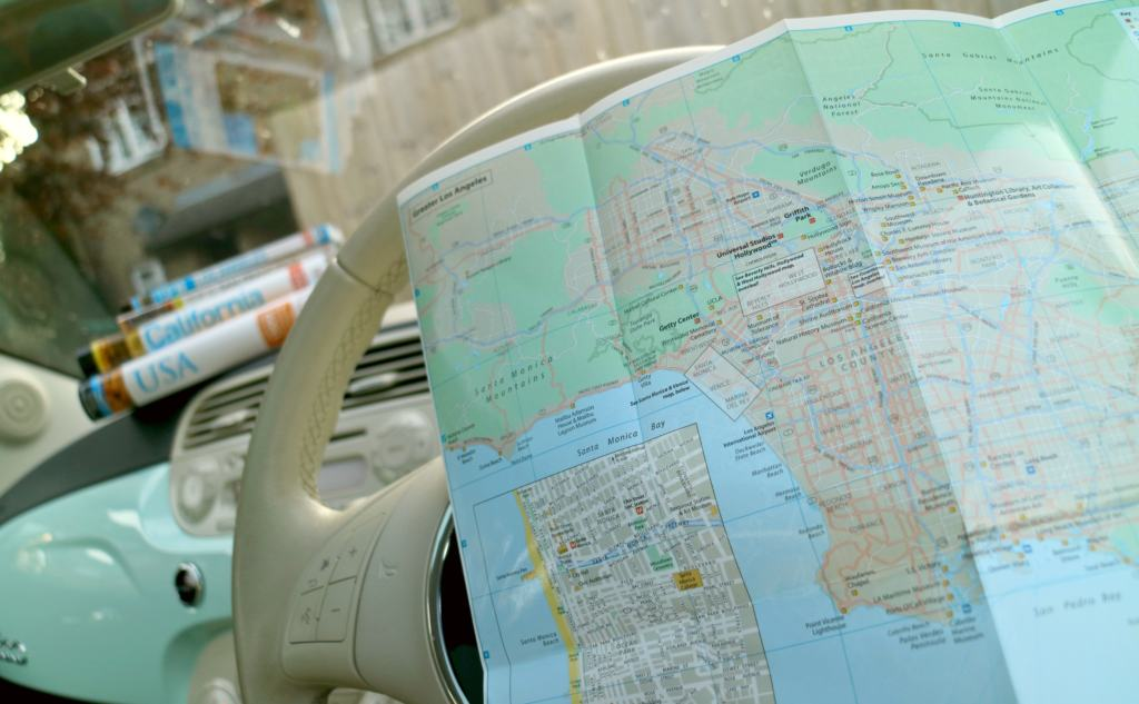 map and travel guides in a car for a US road trip