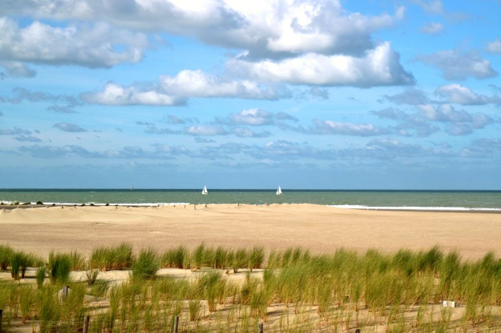 dunkirk beach on a sunny day with sail boats