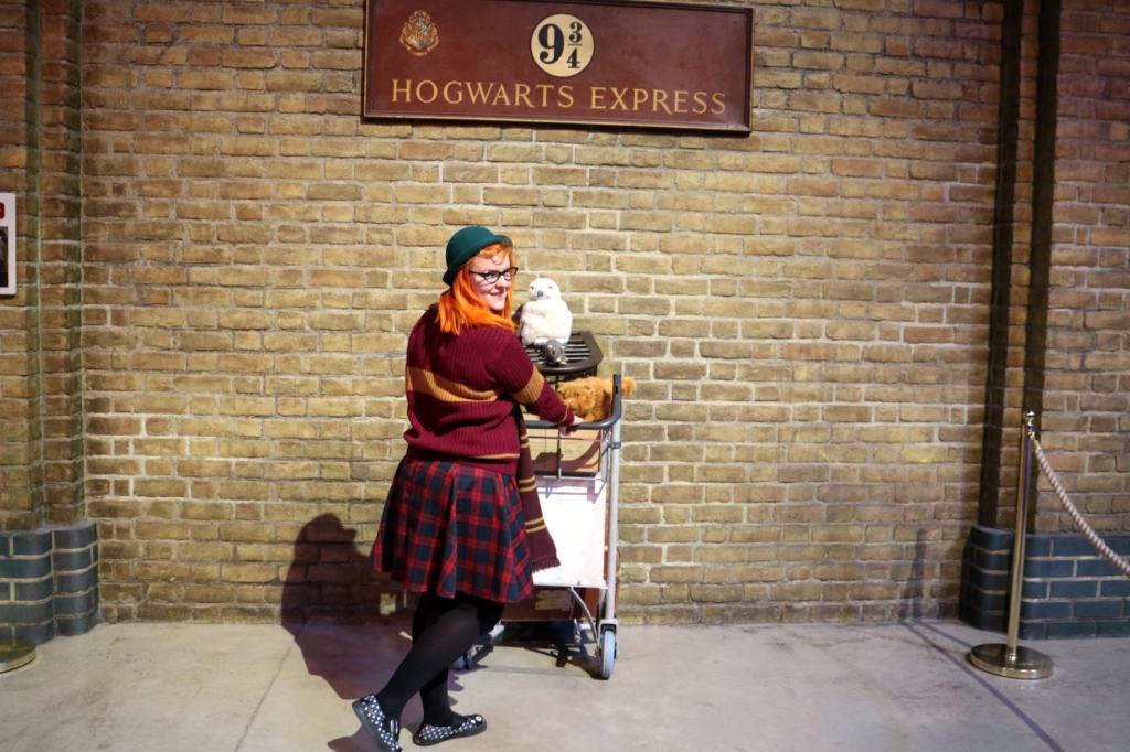 red head girl in front of platform 9 and 3/4 in a Gryffindor uniform at the Harry Potter Studio Tour
