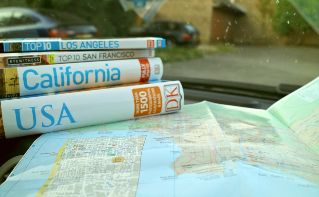 USA travel guides and maps in a car for planning a USA road trip