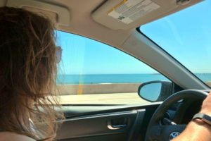long haired male driving inside a car through the Big Sur, California