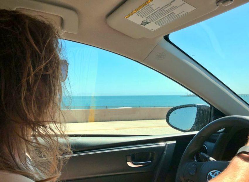 long haired male driving inside a car through the Big Sur, California