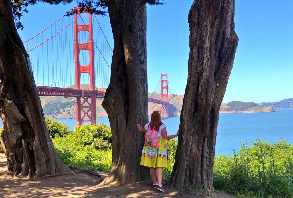 girl holding onto trees in front of the golden gate bridge