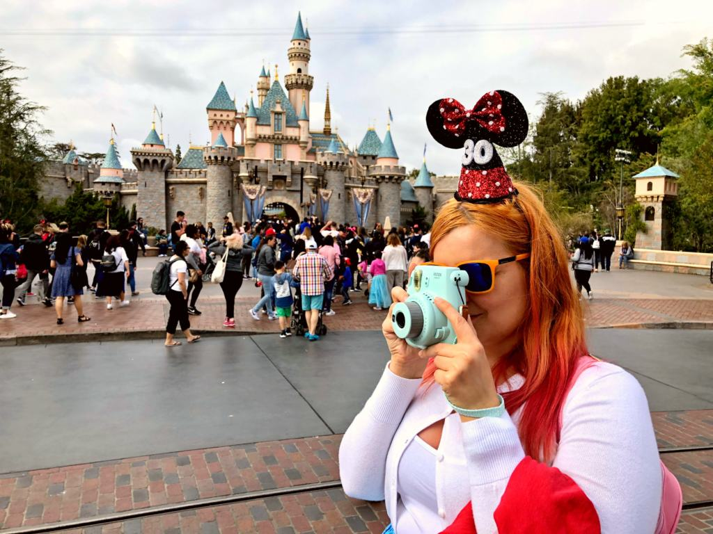 woan with instax camera in front of a castle in disneyland
