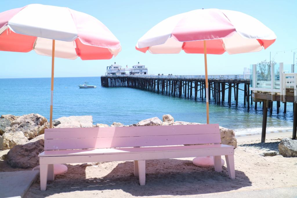 pink bench and sun parasol in front of malibu pier
