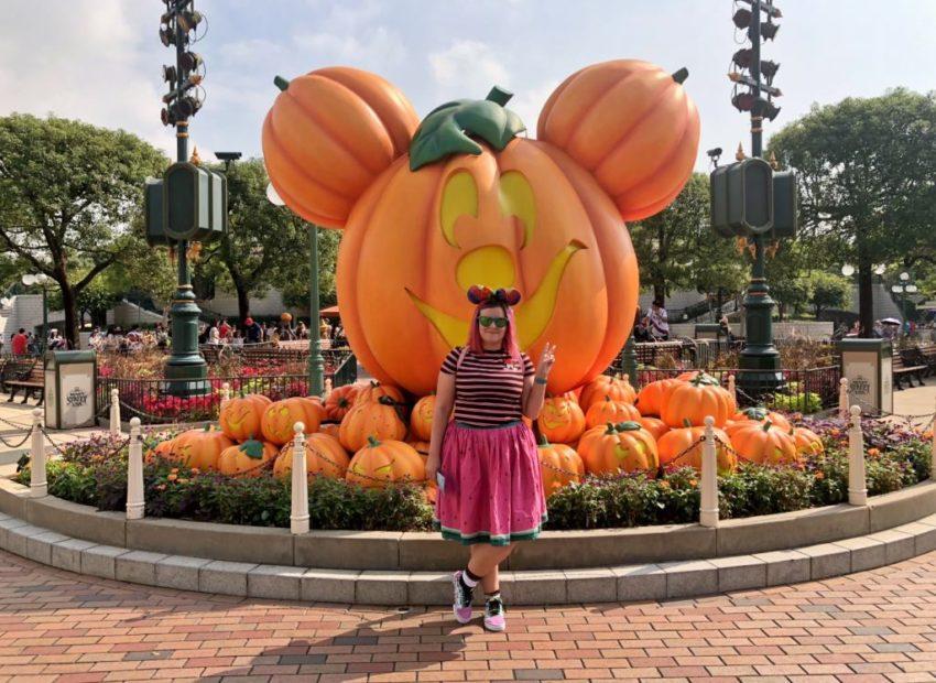 woman in minnie ears in front of a mickey pumpkin in Disneyland