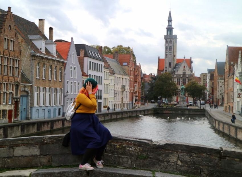 Woman on a bridge in Brugge overlooking a river and chruch
