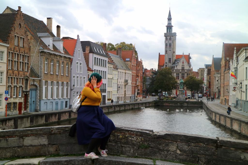 Woman on a bridge in Brugge overlooking a river and church exploring mindful travel