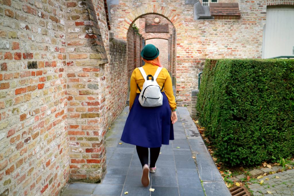 woman walking through an alley in brugge, Belgium on a mindful travel trip