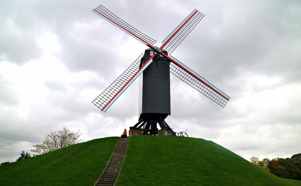Windmill on a hill in Brugge with a woman trying mindful travel