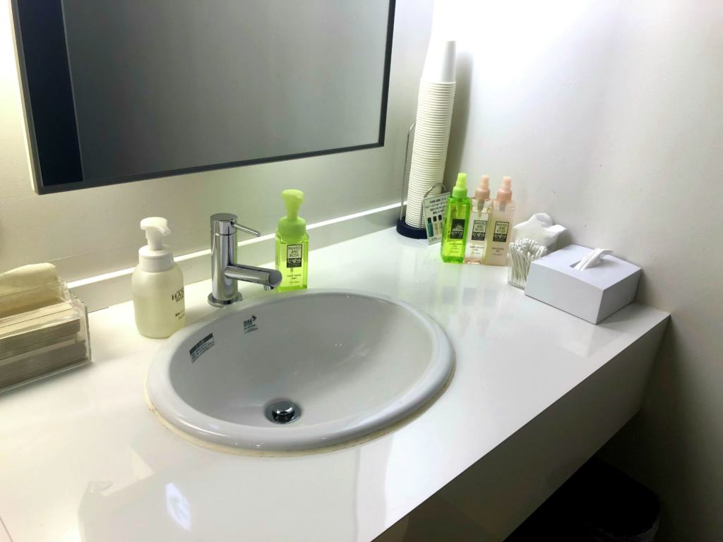 sink of the bathroom in the capsule hotel with products