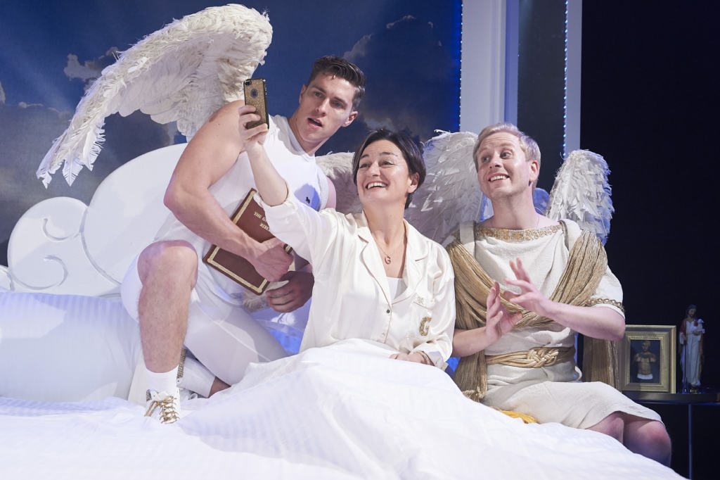 god and the angels taking a selfie on the bed in AN ACT OF GOD
