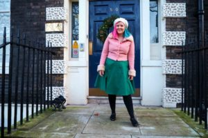 Kariss laughing in green midi dress and pink coat