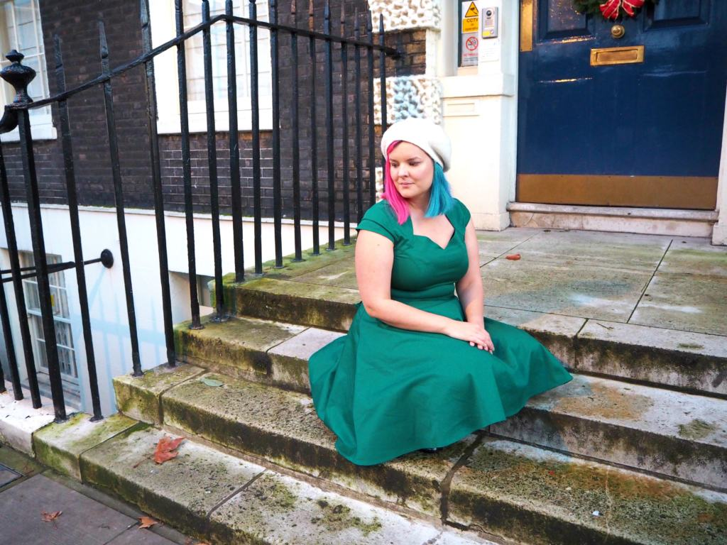 Kariss sat on a step in the Green Midi Dress