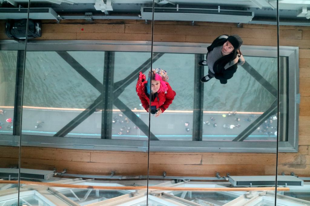 image of Kariss and friend in the mirror above the glass walkway on London Bridge